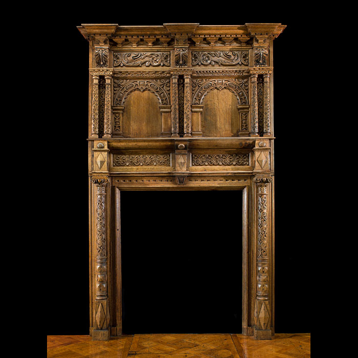 A tall Jacobean carved oak antique fireplace surround