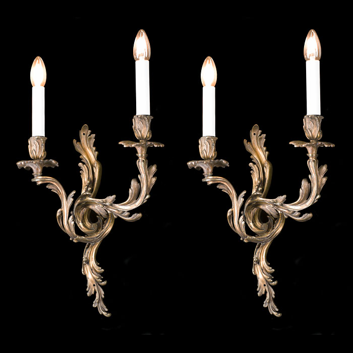 A Rococo style pair of brass wall lights