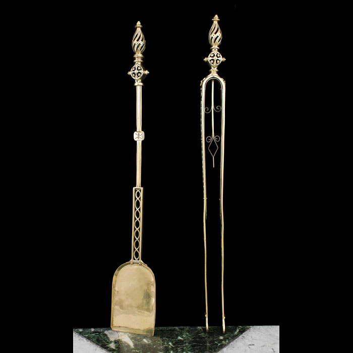 A Gothic Revival pair of brass firetools