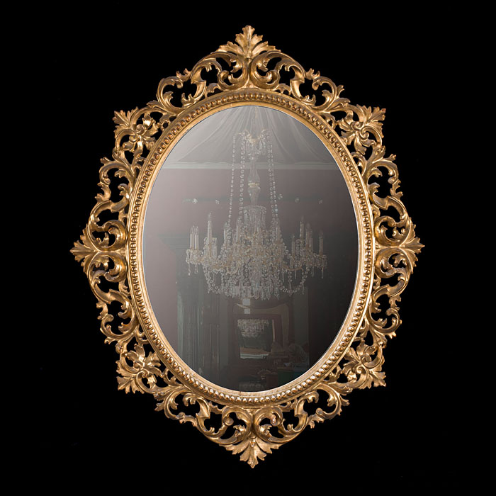 An oval gilded Rococo style wall mirror