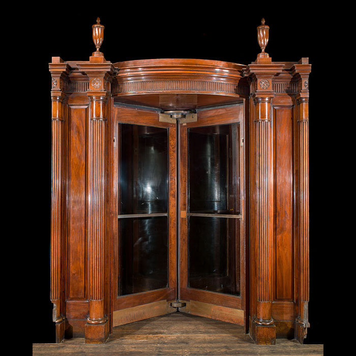 4794: A 1920s carved mahogany revolving doorway decorated with Neoclassical fluted pilasters headed by urns. The  internal revolving doors can be altered to three configurations includes all the mechanical