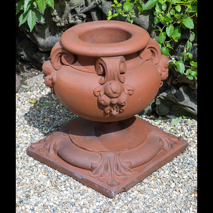 A set of four small antique Regency style terracotta garden urns