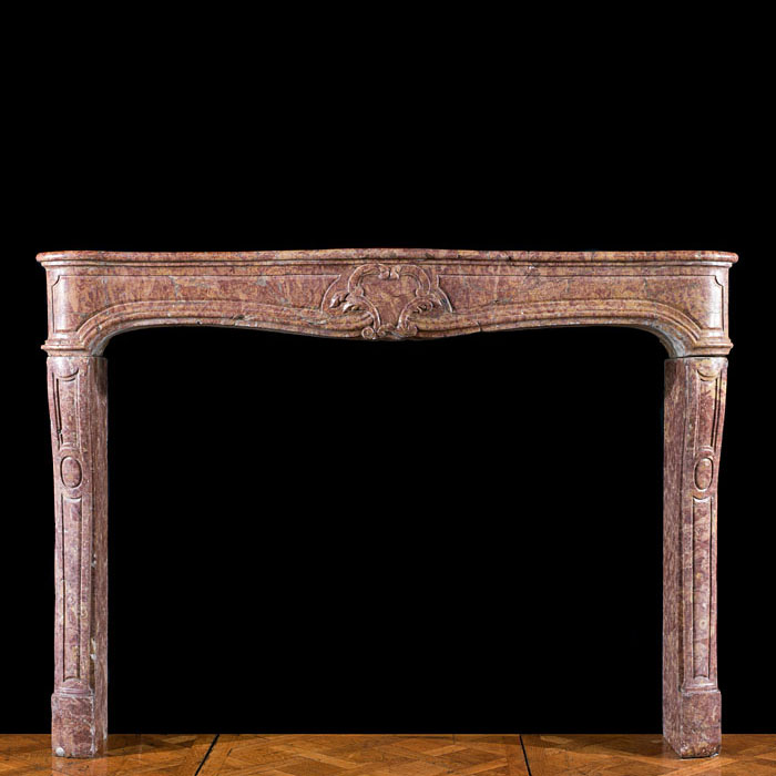 4880: A Louis XV deep rose Brocatello marble fireplace surround. The moulded serpentine shelf above a frieze centred by a simple cartouche, the shaped jambs with moulded panels raised on block feet.French,