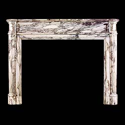 6292: An elegant and chic Louis XVI antique chimneypiece in subtley figured and coloured Breche Viollete marble, the panelled frieze and corner blocks over fluted tapering 3/4 columns.  French ca 1840.   Li