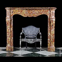 6377: A small well proportioned Pompadour fireplace mantel in Breche D'allepe marble, the serpentine shelf supported on  moulded panelled frieze and jambs, with gilt circular hinged ventilation ports either
