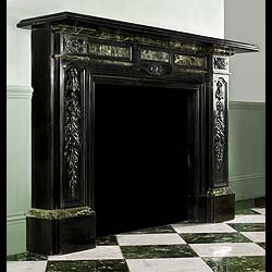 6402: A sophisticated and smart Palladian chimneypiece with rich carved floral and fruit detail on the Belgian Black marble jambs, highlighted with Verde Antico dark green marble panels and mouldings. Engli