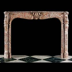 6413: An attractive replica Louis XV chimneypiece in red veined grey marble with a well carved central cartouche on the serpentine shaped frieze beneath the sculpted and shaped shelf flanked by scrolled aca
