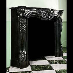 6476: ONE OF A PAIR of beautiful and richly carved large Louis XV Rococo style French Chimneypieces in Namur Black marble. The ornately carved and shaped frieze, beneath the serpentine shelf, is centred by