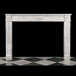 6500: An attractive Louis XVI fireplace surround, in veined Carrara marble, with floral paterae centred on the panelled frieze and the endblocks  and supported on stop fluted scrolled jambs above small foot