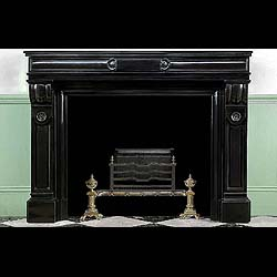 6564: A  Belgian Black Louis XVI fireplace surround, the cushion moulded and panelled frieze, centred by a plain plaque held between stylised shells, is supported on simple corbel topped jambs above small p