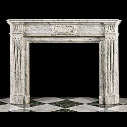 6566: A decoratively veined and carved Arabascato marble chimneypiece in the Louis XVI manner. The volute frieze centred  by a tablet delicately carved with a floral festoon and ribbons, the stop fluted & a