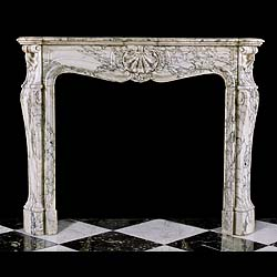 6574: A small and compact Louis XV Rococo style chimneypiece in veinedbreche violette marble. The fielded frieze centred by a stylised shellcartouche beneath a serpentine breakfront shelf flanked by a pair