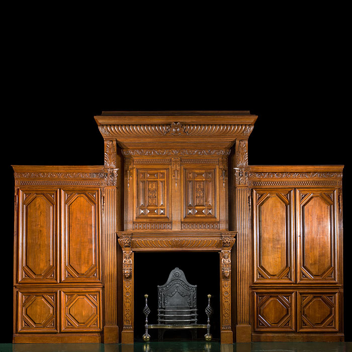 6577: An antique French carved oak chimneypiece and overmantel in the Renaissance style flanked by two full height cupboards concealed behind panelling. The high shaped pediment of the overrmantel is set ab