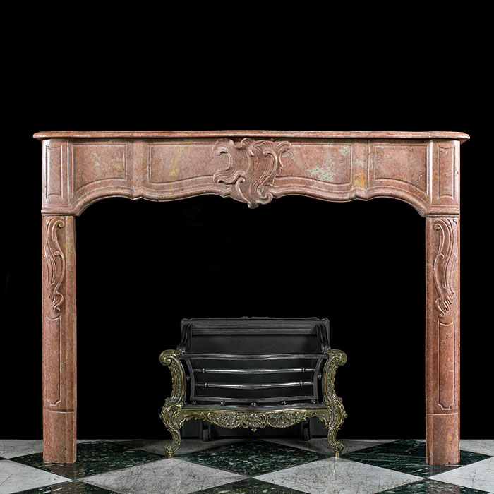 7525: A Louis XIV style antique mantelpiece, in soft pink delicately carved Duquesa Rosa marble with a serpentine shelf and frieze centred by a subtle rocaille decoration, flanked by panelled endblocks abov