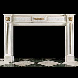 7889: A simple Louis XVI style gilt ormolu chimneypiece in lightly veined white Statuary Marble. The charming central plaque depicting a cherub cavorting amongst scrolling cornucopia flanked by plain gilt o