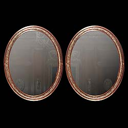 Antique Pair of Oval Mirrors in Bronze with floral adornment   This pair of French Oval mirrors have ornate floral decoration in Bronze. Early 20th century.