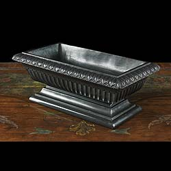 8450:  A small Greek Revival rectangular slate Tazza, the rim carved with lambs tongue motif over continuous fluting supported on a rectangular stepped plinth base.English Regency circa 1830.