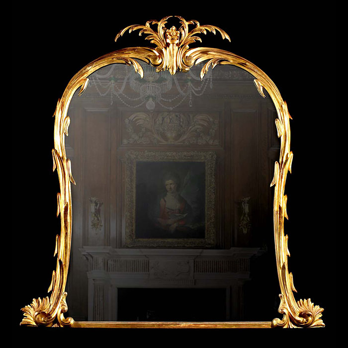 A large carved giltwood Rococo style overmantel mirror