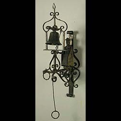 8492:  A wrought iron outside bell the scroll frame mounted with a cloaked figure holding the bell pull above.