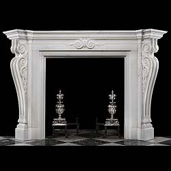 8502: A GRAND AND IMPRESSIVE CARVED WHITE STATUARY MARBLE CHIMNEYPIECE in the Palladian Revival manner.The large moulded breakfront shelf supported over the carved frieze with central scrolled motif continu