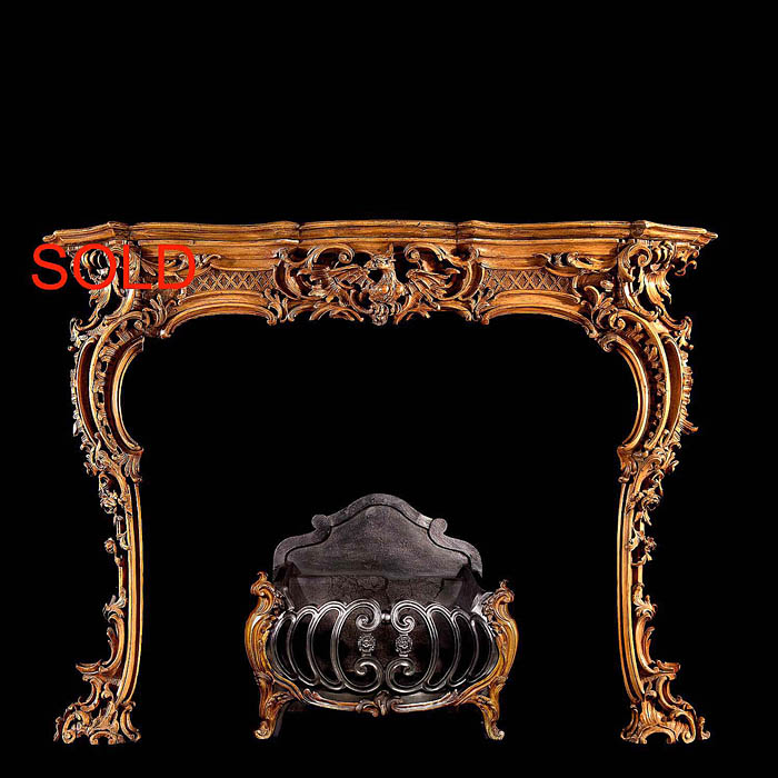 An antique carved pine Georgian Rococo fireplace surround