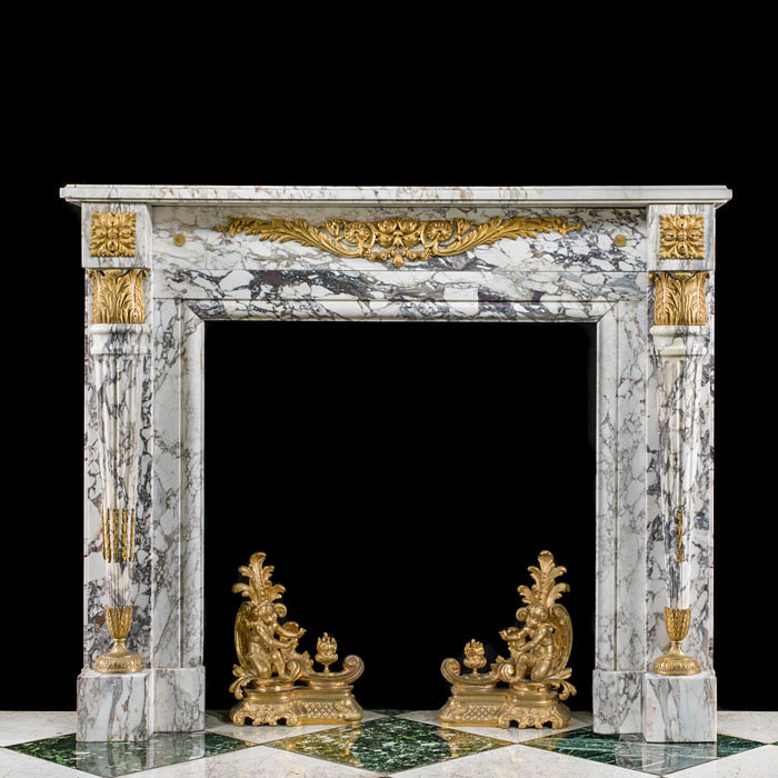 8892: A decorative and chic Louis XVI fireplace mantel in Breche Violette marble with gilt bronze mounts and tapering fluted jambs in the manner of Pierre Gouthiere  (1732-1813)  who was appointed ciseliste
