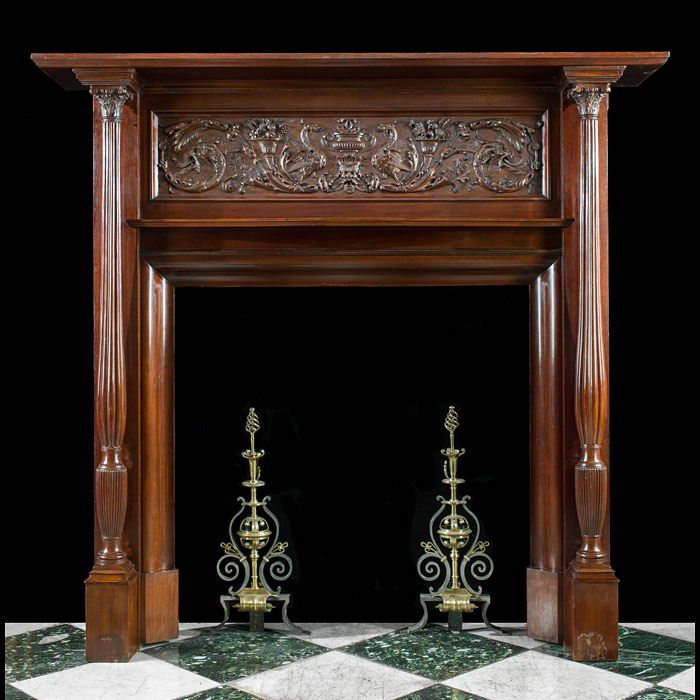 9151: A tall mahogany chimneypiece in the Renaissance Revival manner. The richly carved deep frieze, featuring fruit filled cornucopia, is centred by peacocks facing each other over a gadrooned urn, stylise