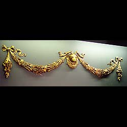 9475:  A large cast gilt bronze decorative overmantle crest with a stags head over laurel wreath ,flanked by ribboned rose , thistle and wheat ear swags .One of a suite of related ornamental crestings
