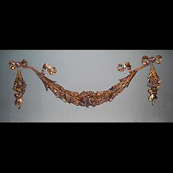 9484: A large decorative gilt bronze floral swag, with ribboned further floral pendants at either end. English 19c.