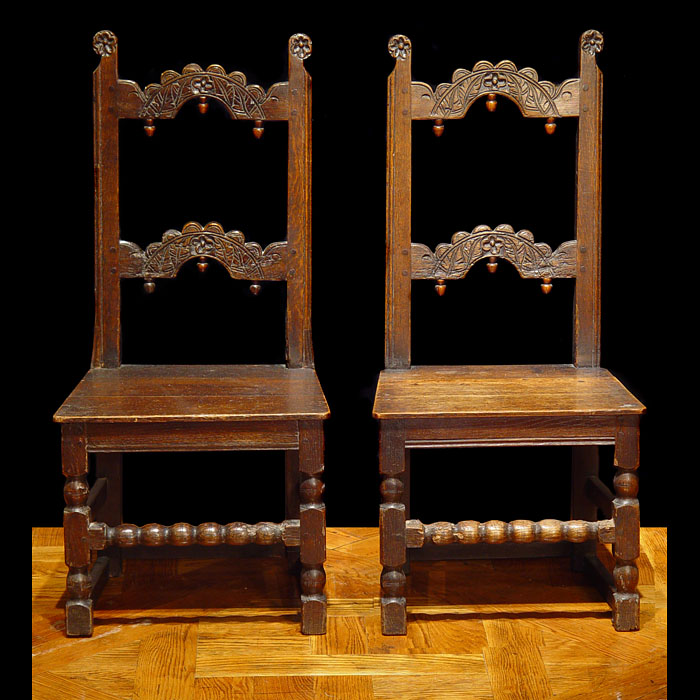 A pair of rare carved oak antique 17th century hall chairs