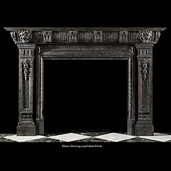 9777: A large and imposing 20th century carved Bluestone fireplace surround in the Renaissance Revival manner,  with lion masks set on the enblocks to either side of a sectioned fluted frieze, the tapering