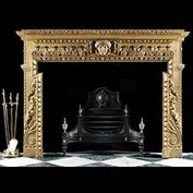 10258:  A boldly carved pine chimneypiece in the early Georgian Palladian manner. The breakfront shelf with carved floral detail over egg and dart undershelf over acathus leafed frieze centred by a lar