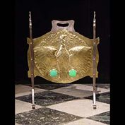 10597: A small and attractive burnished brass firescreen in the Arts & Crafts manner, embossed with a Firebird or Peacock with pair of Opal coloured Cabuchon in the manner of Ruskin, supported on wrought iro