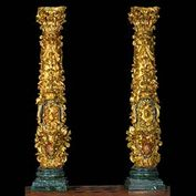 11351:  A PAIR OF TALL PERIOD BAROQUE ORNATELY CARVED GILTWOOD COLUMNS with composite Corithian Ionic capitals. The decoration mostly floral , descending to a tented canopy over winged putti...on later marbl
