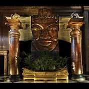 11680: A pair of large teak and granite columns both in four parts, carved overall with dog-tooth and foliate decoration, the columns with later capitals and socles, on granite plinths. Indian, 19th century.