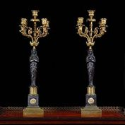 11756: A fine pair of gilt and chocolate patinated bronze five branch candelabra in the French Empire Egyptian Revival manner. There are four branches centered by a further branch, supported on two Pharonic