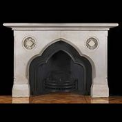 11793: A VICTORIAN CARVED LIMESTONE FIREPLACE IN THE NEO GOTHIC MANNER, the double arch and the inset circular high relief carved star-diamond motif reminiscent of Moorish design.The original register grate