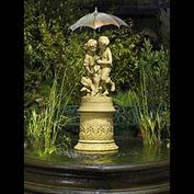 12002: A DELIGHTFULLY DETAILED SMALL TERRA COTTA FOUNTAIN in the Victorian manner, featuring a boy and a girl standing on a a round plinth bedecked with dock leaves and other foliage,sheltering under a rigid