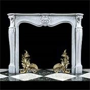12852: A small Rococo fireplace in the Louis XV manner carved in veined Carrara marble with a serpentine breakfront shelf above a central shell cartouche flanked by foliate astragal style decoration above pa