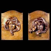 8102: A pair of bronze plaques each cast in high relief with a head of a young girl with flowing hair, signed 'Labour Larroux'.