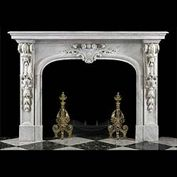 8167: A GRANDLY CARVED LOUIS XIV STYLE CARRARA MARBLE FIREPLACE MANTEL in the French, late Baroque manner. The substantial plain moulded shelf supported over boldly-scrolled brackets atop jambs with descend