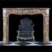 8383: A SMALL AND PRETTY LOUIS XV ROCOCO FIREPLACE in subtly figured red and yellow Breche d'Aleppe marble.The freize under the serpentine shelf with an oval medallion central cartouche flanked by subtly sc