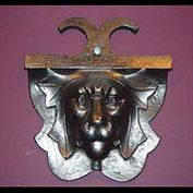 9474:  An Art Deco cast iron Lion's mask wall mounted plaque. The stylised mane in leaf form,  the expression ? ...quizzical or fearsome depending on the lighting. English 1930's.