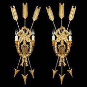 9550:  A pair of two branch wall sconces in the Louis XVI Trophee style, the supports modelled as three arrows piercing a central wreath and ribbons. French early 20th century. Painted carved wood with