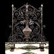 9869: An early 20th century wrought iron firescreen, formed with a classical urn and roses, within scrollwork.  Link to:  Antique Firescreens.